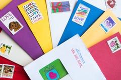 Umschläge von verschiedenen Farben mit Liebes-Stempeln Stockfotos