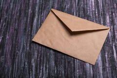 Umschlag des Kraftpapiers Liebesbriefumschlag Hölzerner Hintergrund Dieses ist eine 3D übertragene Abbildung Lizenzfreie Stockbilder