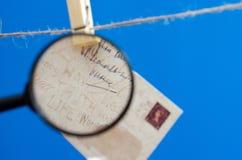 Umschlag durch eine Lupe auf einem Seil auf einem blauen Hintergrund Stockfotos