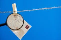 Umschlag durch eine Lupe auf einem Seil auf einem blauen Hintergrund Lizenzfreies Stockfoto