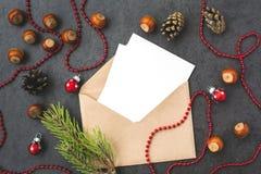 Umschlag, Kegel, Haselnüsse und Weihnachtsdekorationen Stockfotografie