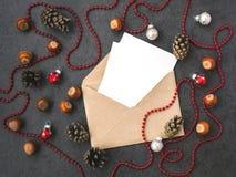 Umschlag, Kegel, Haselnüsse und Weihnachtsdekorationen stockfoto