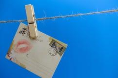 Umschlag mit einem Kuss auf dem Seil auf einem blauen Hintergrund Lizenzfreie Stockfotos