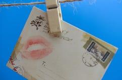 Umschlag mit einem Kuss auf dem Seil auf einem blauen Hintergrund Stockfotos