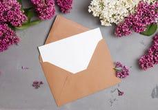 Umschlag mit leerem Papier auf dem grauen Hintergrund mit lila Blumen stockfotos