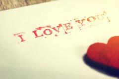 Umschlag mit Mitteilung ich liebe dich und Herzen auf einem hölzernen backgrou Stockbild