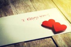 Umschlag mit Mitteilung ich liebe dich und Herzen auf einem hölzernen backgrou Lizenzfreie Stockfotografie