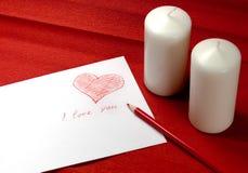 Umschlag mit rotem Innerem und zwei Kerzen Stockfotografie