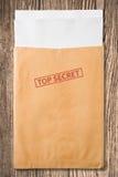 Umschlag mit streng geheim Stempel und unbelegten Papieren. Lizenzfreies Stockbild