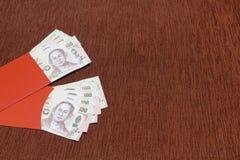 Umschlag mit zwei Rottönen mit Bank des thailändischen Baht als chinesischem Neujahrsgeschenk ` angpao ` Lizenzfreie Stockfotos