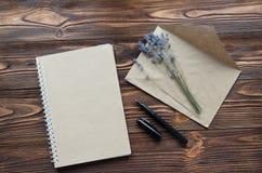 Umschlag, notepade vom Kraftpapier, Stift, trockener Lavendel auf hölzernem stockfotografie