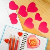 Umschlag, rosafarbene Blume, Bleistifte und stilisierte Herzen Stockfoto