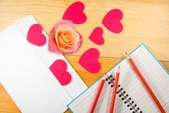 Umschlag, rosafarbene Blume, Bleistifte und stilisierte Herzen Lizenzfreie Stockbilder