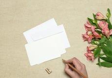 Umschlag und Postkarte mit Blumen auf Steinhintergrund stockfoto