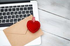Umschlag und rotes Herz liegen auf der Laptoptastatur Lizenzfreie Stockbilder