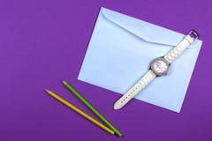 Umschlag, zwei Bleistifte und Frauenuhr auf purpurrotem Hintergrund Flache Lage Lizenzfreies Stockfoto