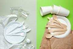 Umweltfreundliches Einweggeschirr machte vom Bambusholz und vom Papier auf einem grünen Hintergrund Schädliche Plastikteller und  lizenzfreies stockbild
