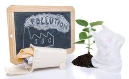 Umweltkonzept mit einem grünen Pflänzchen, einem Abfalleimer und Th Lizenzfreies Stockfoto
