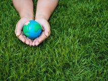 Umweltslogans, Sprechen und Phrasen über die Erde, die Natur und das gehende Grün Erde in den Händen und im grünen Rasenflächehin Stockfotos