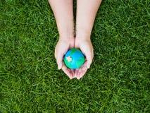 Umweltslogans, Sprechen und Phrasen über die Erde, die Natur und das gehende Grün Erde in den Händen und im grünen Rasenflächehin Lizenzfreie Stockbilder