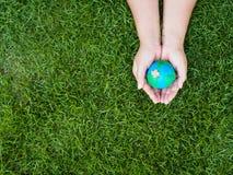 Umweltslogans, Sprechen und Phrasen über die Erde, die Natur und das gehende Grün Erde in den Händen und im grünen Rasenflächehin Lizenzfreies Stockfoto