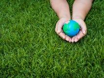 Umweltslogans, Sprechen und Phrasen über die Erde, die Natur und das gehende Grün Erde in den Händen und im grünen Rasenflächehin Stockbild