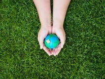 Umweltslogans, Sprechen und Phrasen über die Erde, die Natur und das gehende Grün Erde in den Händen und im grünen Rasenflächehin Lizenzfreies Stockbild