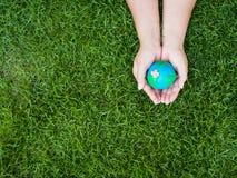 Umweltslogans, Sprechen und Phrasen über die Erde, die Natur und das gehende Grün Erde in den Händen und im grünen Rasenflächehin Stockfoto