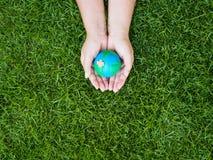 Umweltslogans, Sprechen und Phrasen über die Erde, die Natur und das gehende Grün Erde in den Händen und im grünen Rasenflächehin Lizenzfreie Stockfotografie