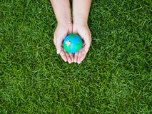 Umweltslogans, Sprechen und Phrasen über die Erde, die Natur und das gehende Grün Erde in den Händen und im grünen Rasenflächehin Lizenzfreie Stockfotos