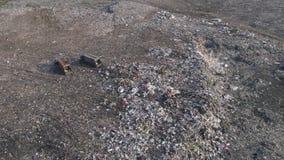 Umweltverschmutzungsproblem, Brummenansicht über Leute arbeiten am Dump nahe LKWs und fliegenden Seemöwen über großem Abfall stock footage
