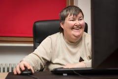 Umysłowo - niepełnosprawny kobiety obsiadanie przy komputerem, edukacją i L, zdjęcie royalty free