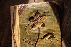 Un álbum de foto hecho a mano con la flor en fondo de madera imagenes de archivo