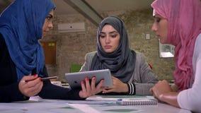 Un árabe femenino en hijab azul está señalando a otras muchachas musulmanes en la tableta, humor de trabajo, conversación con los metrajes