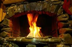 Un árbol ardiente en una chimenea del hogar del ladrillo, una llama en una parte posterior de la oscuridad Fotos de archivo libres de regalías