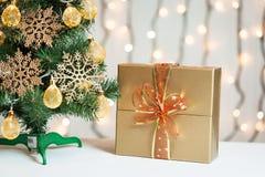 Un árbol de navidad adornó copos de nieve y una guirnalda con la caja de regalo en el fondo de un bokeh Imagenes de archivo