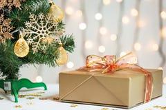 Un árbol de navidad adornó copos de nieve y una guirnalda con la caja de regalo en el fondo de un bokeh y de tableros blancos Foto de archivo libre de regalías