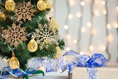 Un árbol de navidad adornó copos de nieve y una guirnalda con la caja de regalo en el fondo de un bokeh y de tableros blancos Fotografía de archivo