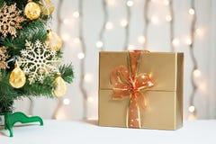Un árbol de navidad adornó copos de nieve y una guirnalda con la caja de regalo en el fondo de un bokeh y de tableros blancos Fotografía de archivo libre de regalías