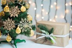 Un árbol de navidad adornó copos de nieve y una guirnalda con la caja de regalo en el fondo de un bokeh y de tableros blancos Fel Imagenes de archivo