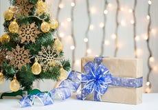 Un árbol de navidad adornó copos de nieve y una guirnalda con la caja de regalo en el fondo de un bokeh y de tableros blancos Fel Foto de archivo