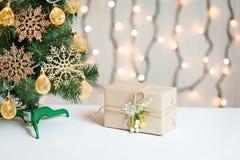 Un árbol de navidad adornó copos de nieve y una guirnalda con la caja de regalo en el fondo de un bokeh y de tableros blancos Fel Foto de archivo libre de regalías