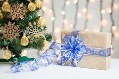 Un árbol de navidad adornó copos de nieve y una guirnalda con la caja de regalo en el fondo de un bokeh y de tableros blancos Fel Fotos de archivo libres de regalías