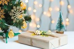 Un árbol de navidad adornó copos de nieve y una guirnalda con la caja de regalo en el fondo de un bokeh y de tableros blancos Fel Fotografía de archivo