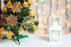 Un árbol de navidad adornó copos de nieve y una guirnalda con la linterna en el fondo de un bokeh y de tableros blancos Feliz Nav Imagen de archivo libre de regalías