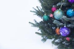 Un árbol de navidad adornado afuera con las chucherías coloridas hechas del vidrio foto de archivo