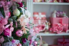 Un árbol de navidad festooned completamente con las decoraciones de la Navidad En el fondo, el niño juega, que desaparece en la f Foto de archivo