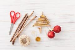 Un árbol de navidad hecho en casa hecho de ramas con las bolas rojas de la Navidad en blanco Fotos de archivo libres de regalías