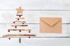 Un árbol de navidad de madera con las bayas de un viburnum y de un envelo imagenes de archivo