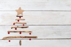 Un árbol de navidad de madera y las bayas de un viburnum en un blanco cortejan imagen de archivo libre de regalías